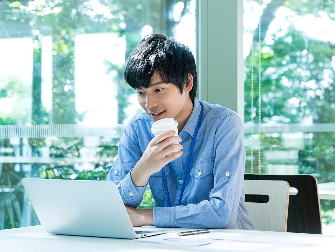 コーヒーを飲みながらパソコンを見ている男性